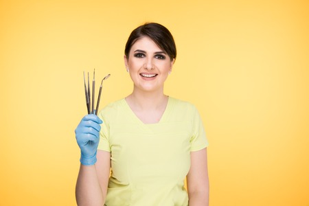 Woman dentist posing with dental tools isolated over the yellow background.