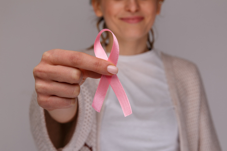 Womans hand holding pink ribbon isolated.
