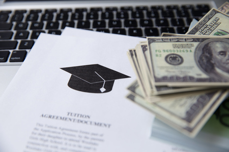 Tuition fee or student loan with calculator. Education price , savings fund college, and expenses concept. Money and papers on table. Stock Photo