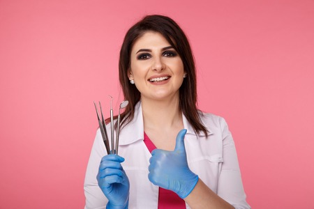 Woman dentist posing with dental tools isolated over the pink background. Stock Photo