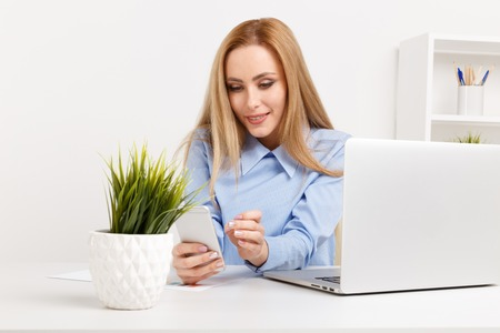 Photo of smiling businesswoman sitting at office and working. Using phone in office.