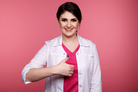 Dentist showing thumb and smiling isolated over the pink background.