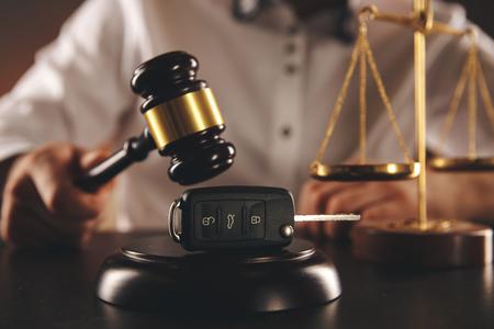 Close up of judge gavel and car keys over soundboard on white