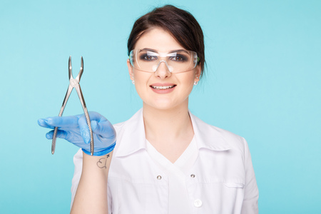 Woman dentist posing with dental tools isolated over the blue background.
