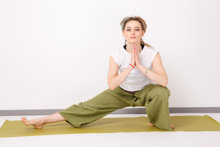 Female model in yoga pose in the studio. Young woman doing exercises. Relax Stock Photo