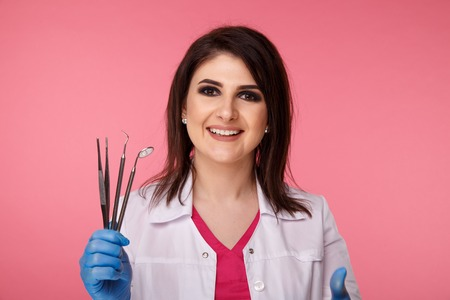 Pretty yong dentist in blue gloves with medical tool isolated over the pink background.