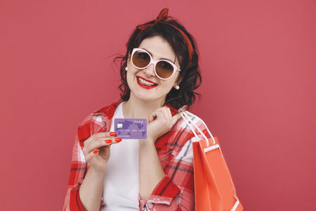 Portrait of happy nice girl with curly hair holding bags and credit card after shopping Stock Photo