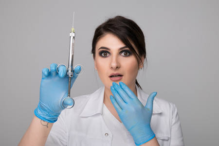 Closeup photo of female dentist holding oral syringe isolated over the grey backgrownd.