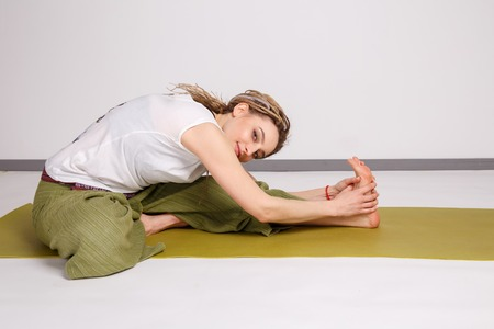 Young female doing yoga on the mat.