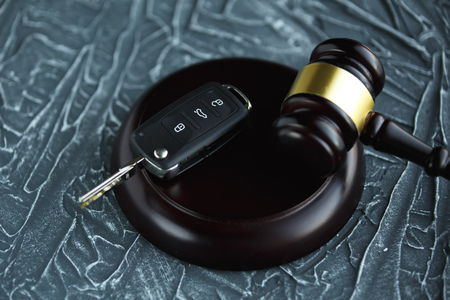 Close-up Of Gavel And Car Key On Sounding Block Against Stock Photo