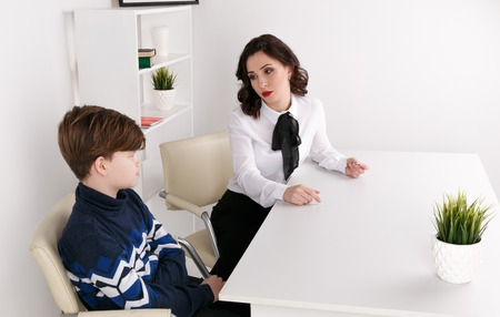 Young brunnette female talking to the boy indoor the white room. Psychologist woman with patiant. Psychology therapy. Stock Photo