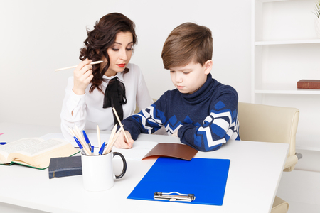 Female teacher helps teen boy to do his homework. Doing homework together. Stock Photo
