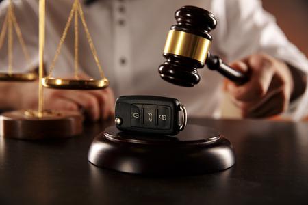 Cerca del mazo del juez y las llaves del coche sobre la caja de resonancia en blanco Foto de archivo