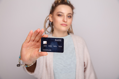 Young woman holding dark blue credit card isolated over the grey background.