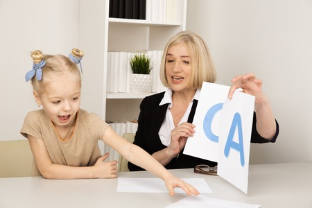 Speach therapy concept. Girl with therapist learning right pronunciation. Stock Photo