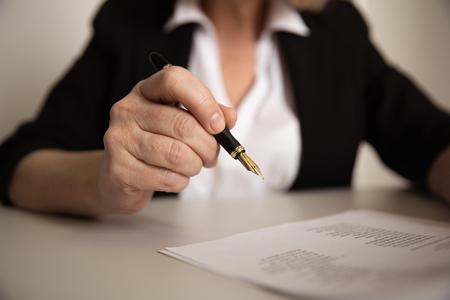 Weibliche Büroangestellte schreiben auf Papierdokumenten mit Stift.