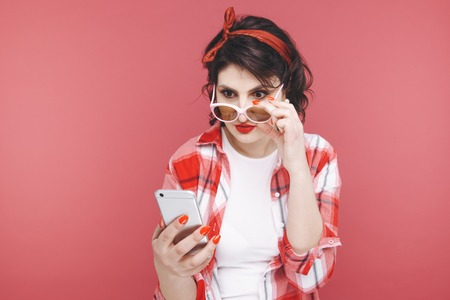 Portrait of an excited beautiful girl wearing red shirt, holding mobile phone isolated over pink background. Stock Photo