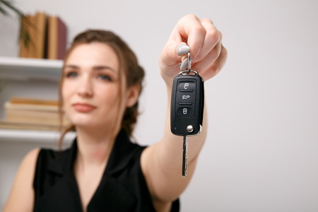 Female car seller giving keys after saling auto.