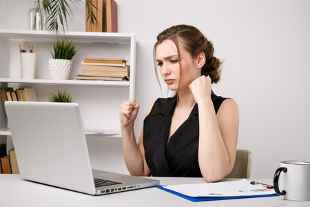 Nervous andangry woman in office closing her computer
