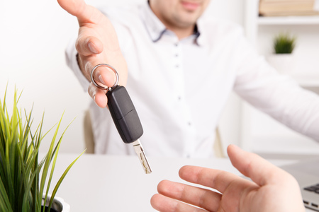 Male seller sales a car and giving keys to new owner.
