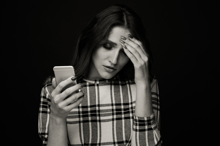 Sad teen being victim of cyber bullying online sitting on a couch in the living room at Stock Photo