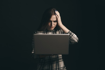 Teen girl excessively sitting at the computer laptop at home. he is a victim of online bullying Stalker social networks Stock Photo - 125519092
