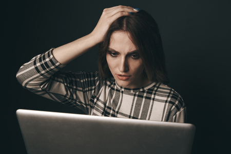 Teen girl excessively sitting at the computer laptop at home. he is a victim of online bullying Stalker social networks