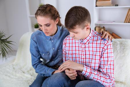 Coppia sconvolta seduta a casa. Problema nel concetto di coppia. Archivio Fotografico