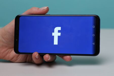 Tula, Russia - November 28, 2018: Facebook social media app logo on log-in, sign-up registration page on mobile app screen on smart devices in business persons hand at Editorial