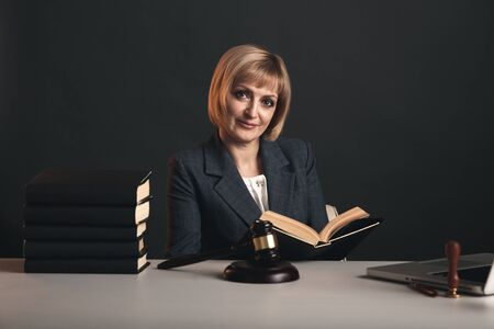 Blonde female advocate at the workplace isolated in studio reading book.
