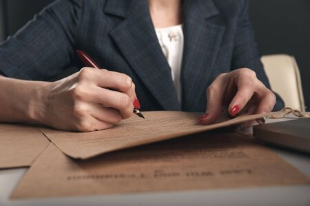 Closeup view of woman attorney writing on documents by pen.