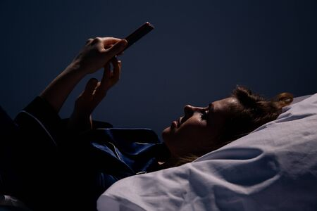 Girl lying in the bed and using cellphone at night. Stok Fotoğraf