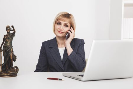 Female lawyer in the office sitting and working with paper and laptop.