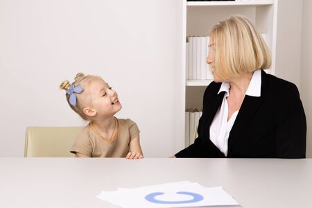 Girl with therapist training speach in cabinet. 스톡 콘텐츠