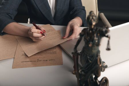 Themis on the desk on the front view and paper documents behind. Stockfoto