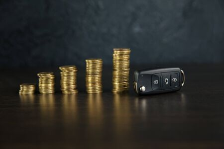 Close-up Of Car Key In Front Of Coins Stacked On Wooden Table Foto de archivo