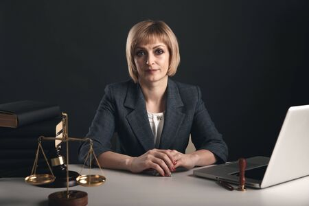 Woman lawyer reading professional books in office. Wooden gavel and libra on the desk. Stock Photo