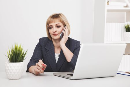 Zajęty sekretarka kobieta w biurze. Działający laptop i telefon.