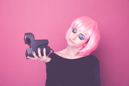 Young stylish woman holding retro camera and standing in a pink wig in a bright studio.