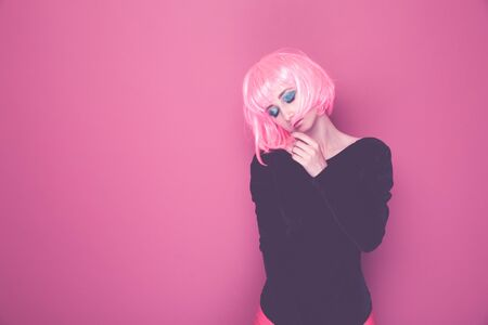 Closeup portrait of young pretty woman in 90s style in pink wig standin isolated in a bright studio.