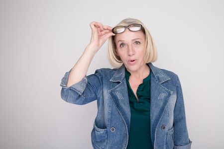 Amazed and exited blond woman opened her mouth and put up her glasses in a white studio.