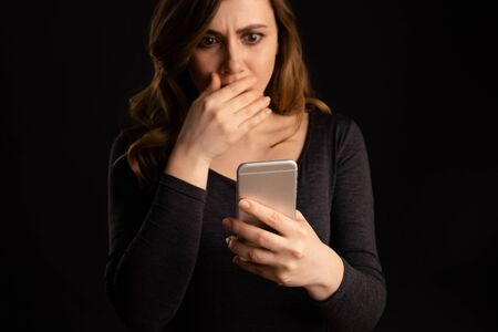 Frightened young woman holding mobile closing her mouth by arm.