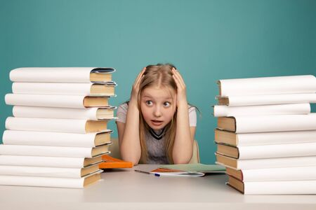 Tired teen girl with books on the background of a school board looking at camera. Space for text Imagens