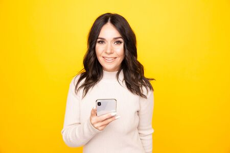 Smiling pretty woman with phone standing isolated on the yellow background. Stock Photo