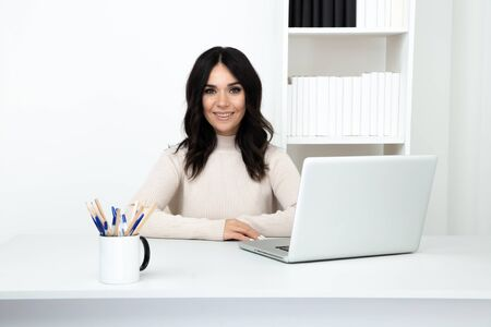 Pretty female worker in office isolated sitting at the desk with computer.