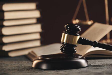 Concept de droit - Livre de droit ouvert avec un marteau de juges en bois sur une table dans une salle d'audience ou un bureau des forces de l'ordre sur fond bleu. Banque d'images