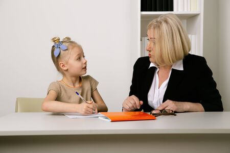 Teacher and pupil concept. Tutor helping with homework to little girl.