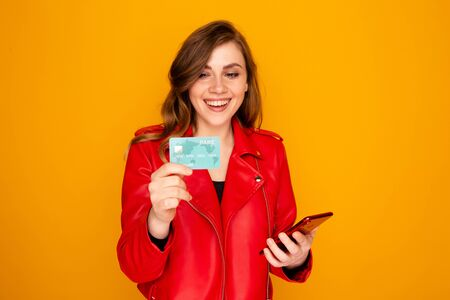 Young woman holding credit card with phone and smiling. Stock Photo