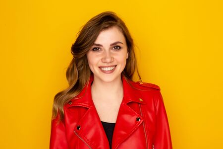 Portrait of pretty young woman in the red clothes isolated over the yellow background.