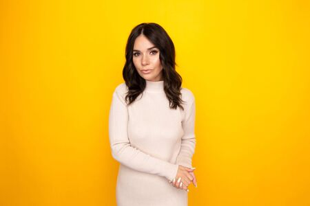 Portrait of pretty young woman standing isolated the yellow background. Stock Photo